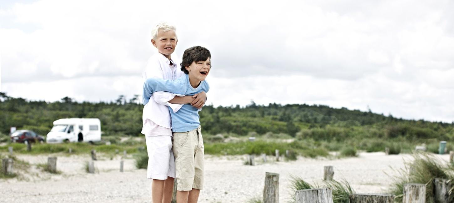 2 boys at the beach in front of a camper