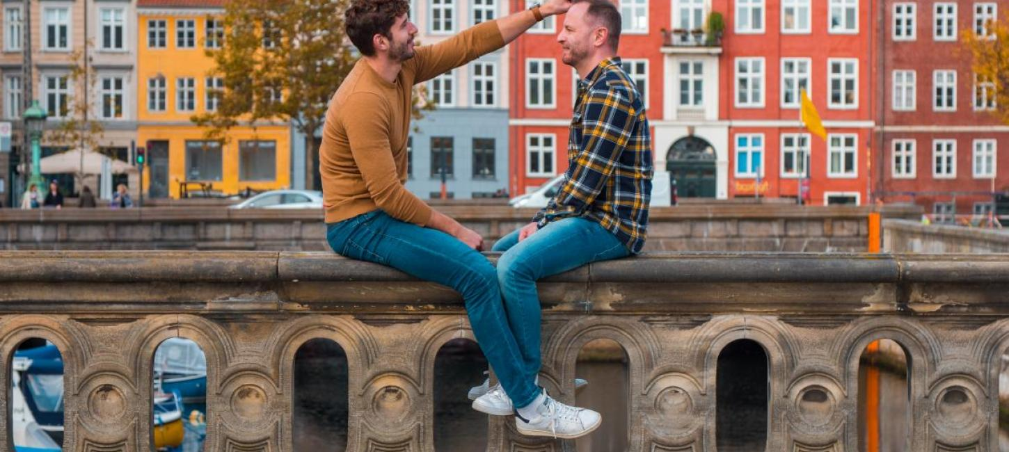 Gay couple sits at the canals in Copenhagen