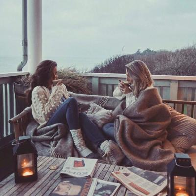Two women having a cozy time on the terrace at Helenekilde Badehotel in Tisvilde during winter.