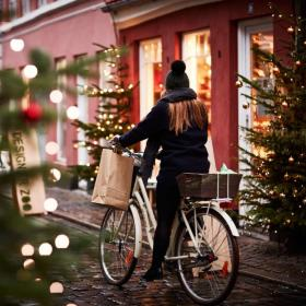 A girl rides a bike through a Christmassy street in Aarhus, Denmark